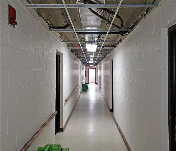 A cleaned apartment complex hallway with ceiling tiles removed