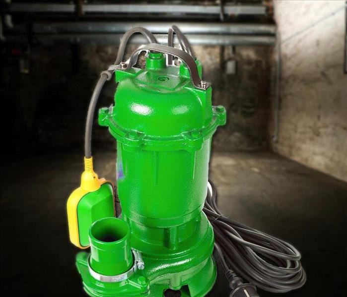 a green colored sump pump in a basement