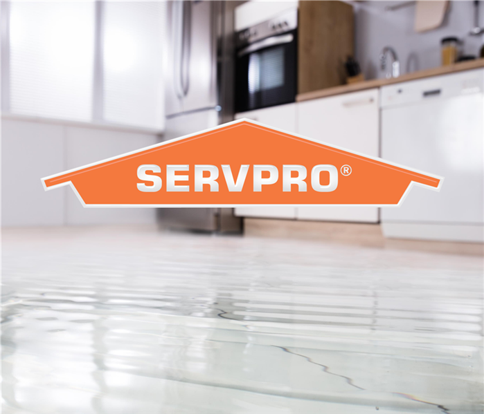 A flooded kitchen with a SERVPRO logo